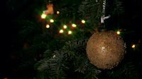 Golden Christmas Ball With Colored Dots And Lights In Background